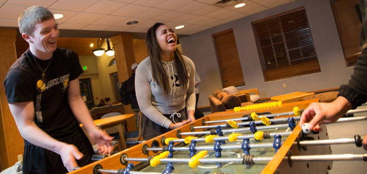 Students playing table foosball in a residence hall