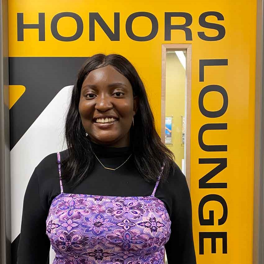 Sefunmi smiles for a photo in front of the Honors Lounge