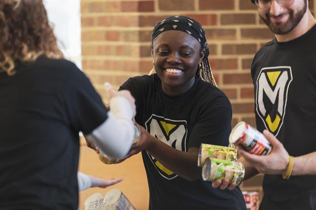 Manchester students collect cans during U Can Crush Hunger.