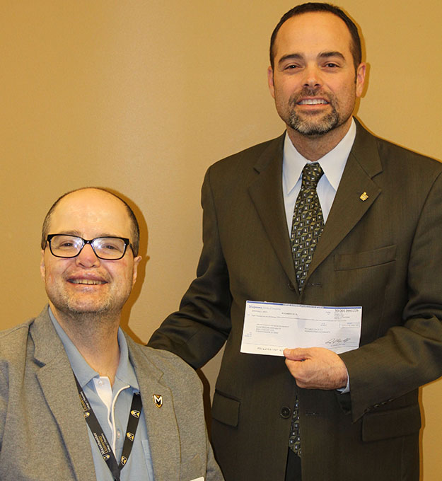 Randy Jennings, right, presents $8,000 to  W. Thomas Smith, dean of Pharmacy Programs at Manchester.