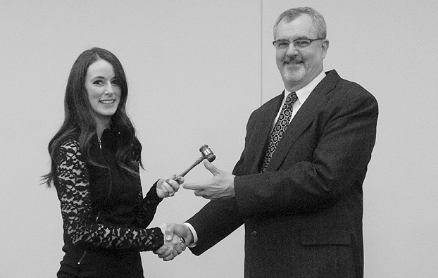 Alexis Young passes the Chamber gavel to Chris Garber in January 2015.
